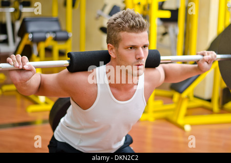 Handsome young man doing squats in gym with barbell - Stock Photo