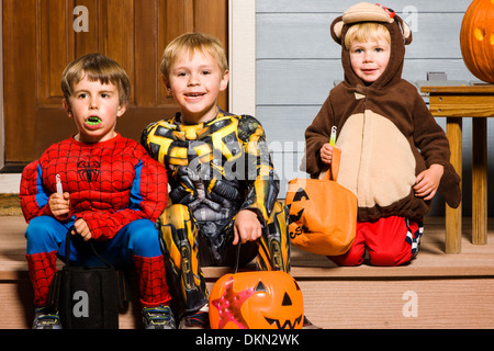 Young children dressed in costume for Halloween Trick-or-Treating - Stock Photo