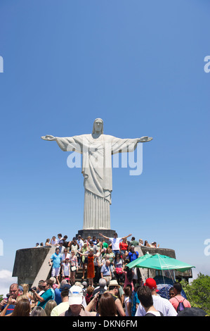 Crowds of tourists visit the Christ monument at Corcovado posing with outstretched arms Rio de Janeiro Brazil - Stock Photo
