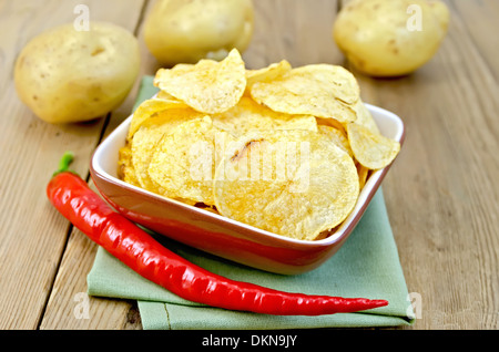 Potato chips in a clay bowl with fresh red chili peppers, fresh potatoes on the background of wooden boards - Stock Photo