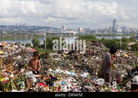 Children scavenging for anything of value within the Inayawan Landfill waste site,Cebu City,Philippines - Stock Photo