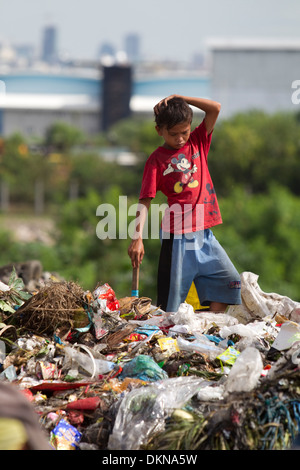 A child scavenging for anything of value within the Inayawan Landfill waste site,Cebu City,Philippines - Stock Photo