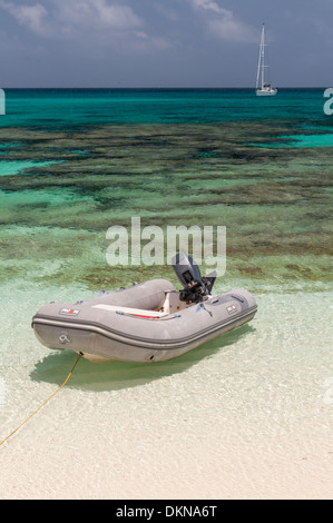 Dinghy on sand beach with coral underwater and yacht at anchor off Huon Island, Huon Atoll, New Caledonia, South - Stock Photo