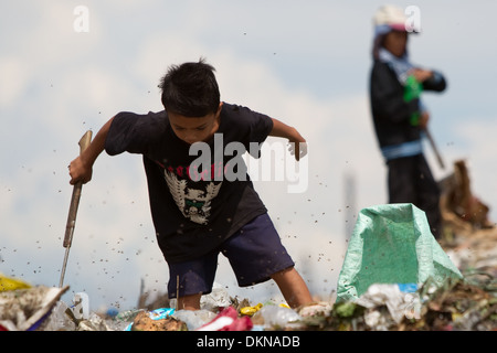 A child surrounded by flies,scavenging for anything of value within the Inayawan Landfill waste site,Cebu City,Philippines - Stock Photo