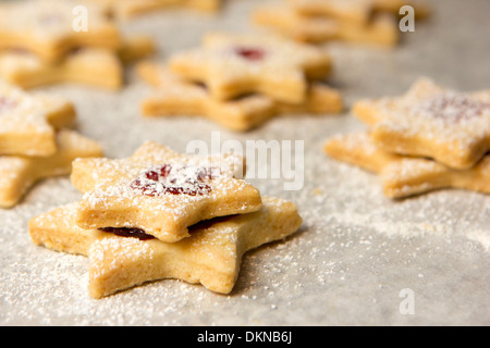 christmas cookies as stars with jam on baking paper - Stock Photo