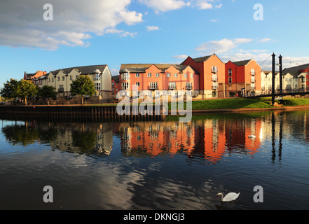 Evening sum illuminates pink brick apartments beside a river with reflections. - Stock Photo