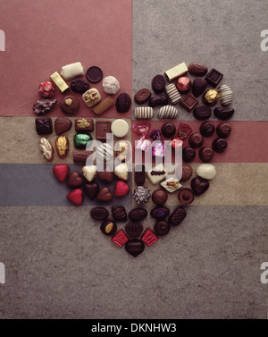A heart shape made from a selection of seven different brands of chocolates on a background of different marbled - Stock Photo
