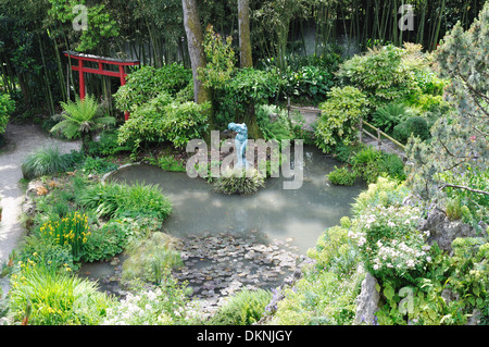 A pond in the Andre Heller Botanical Gardens, Gardone Riviera, Lake Garda, with a sculpture in the style of the - Stock Photo