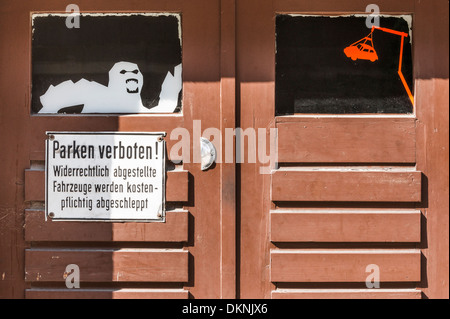 wooden garage door displaying a  no-parking zone  sign and the image of a ghost and a car on the hook of a tow away - Stock Photo