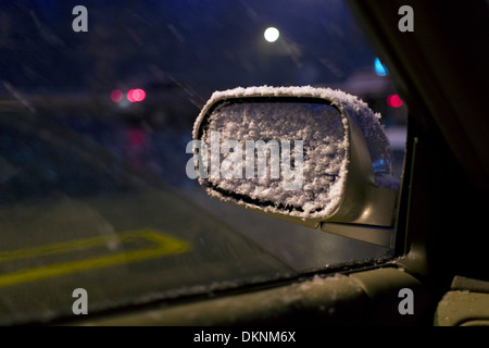 Rear view mirror laden with snow as seen through the side window of a car in a parking lot. - Stock Photo