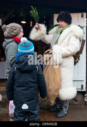 A man dressed up as Rumpodich, the Spree Forest's equivalent to Santa's little helper, gives small presents to children - Stock Photo