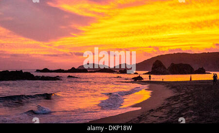 San Agustinillo, Oaxaca State, Mexico. 8th Dec, 2013. Flaming sky of spectacular tropical sunset is reflected by - Stock Photo
