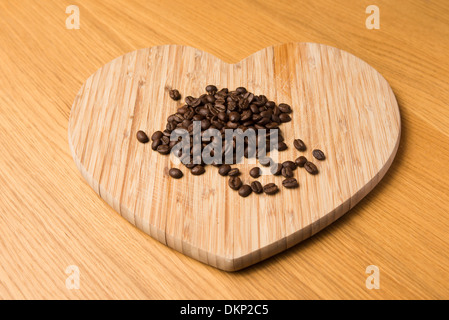 Brown roasted coffee beans on a wooden heart shaped chopping board - Stock Photo