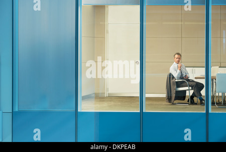 Businessman sitting in conference room - Stock Photo