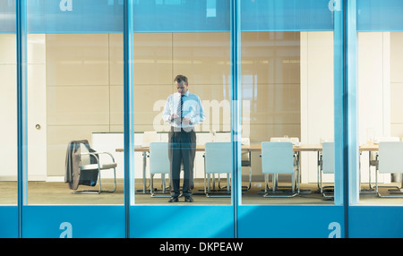 Businessman standing in conference room - Stock Photo