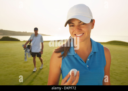 Woman holding golf ball on course - Stock Photo