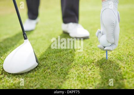 Man teeing golf ball on course - Stock Photo