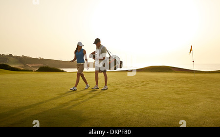 Caddy and woman walking on golf course overlooking ocean - Stock Photo