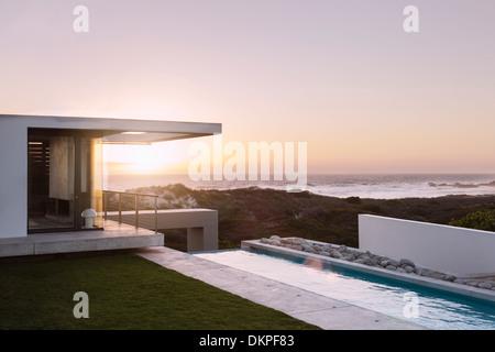 Modern house overlooking ocean at sunset - Stock Photo