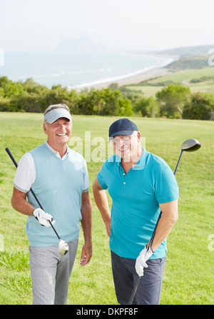 Senior men smiling on golf course overlooking ocean - Stock Photo