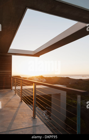 Balcony of modern house overlooking ocean at sunset - Stock Photo