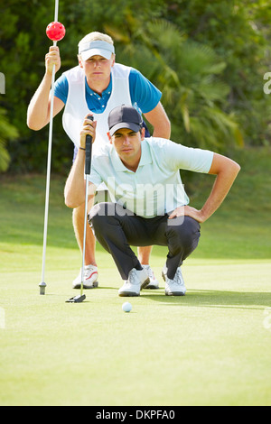 Caddy and golfer on putting green - Stock Photo