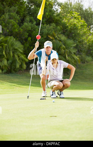 Caddy and golfer preparing to putt - Stock Photo