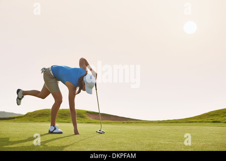 Woman reaching for ball in hole on golf course - Stock Photo