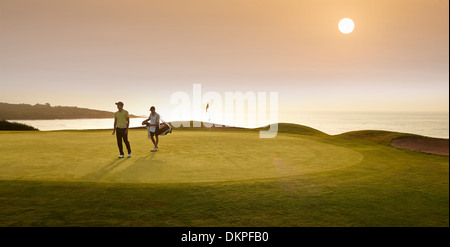 Golfer and caddy walking on golf course - Stock Photo