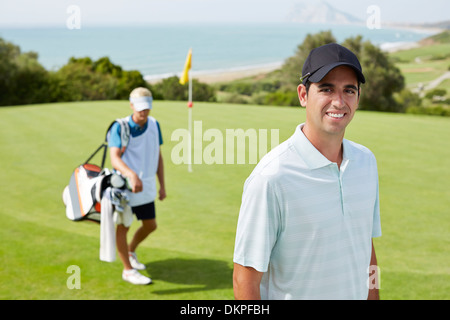 Caddy and golfer on golf course - Stock Photo