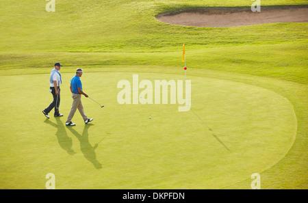 Senior men walking toward flag and hole on golf course - Stock Photo