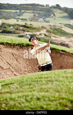 Man swinging from sand trap on golf course - Stock Photo