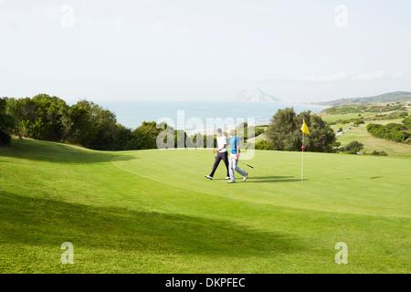 Men walking on golf course overlooking ocean - Stock Photo