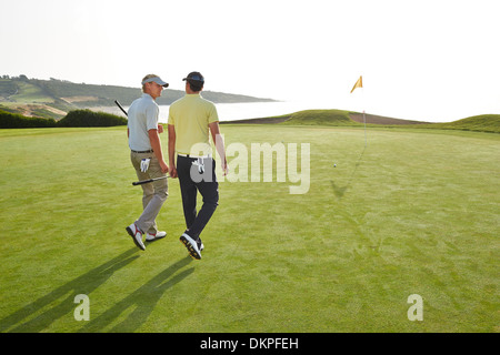 Men walking toward hole on golf course overlooking ocean - Stock Photo