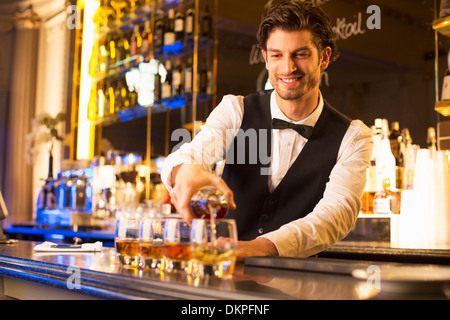 Well dressed bartender pouring bourbon at luxury bar - Stock Photo