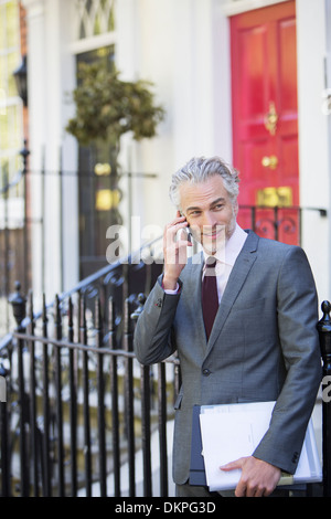 Businessman talking on cell phone on front stoop - Stock Photo