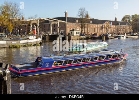 AMSTEL RIVER AMSTERDAM HOLLAND WITH SIGHTSEEING BOATS FULL OF TOURISTS NEAR THE HERMITAGE AND MAGERE BRIDGE - Stock Photo