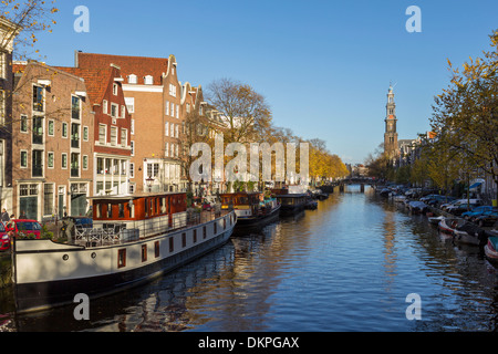 AMSTERDAM  NETHERLANDS THE PRINSENGRACHT CANAL WITH HOUSEBOATS AND THE WESTERKERK TOWER - Stock Photo