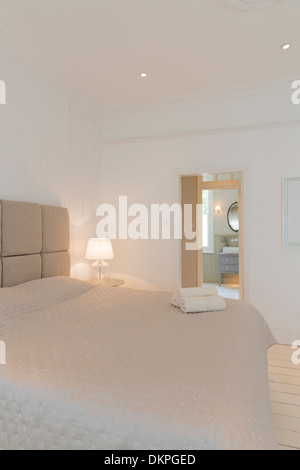 Bed and towels in modern bedroom - Stock Photo