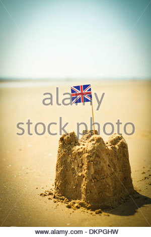 British flag in sandcastle on beach - Stock Photo