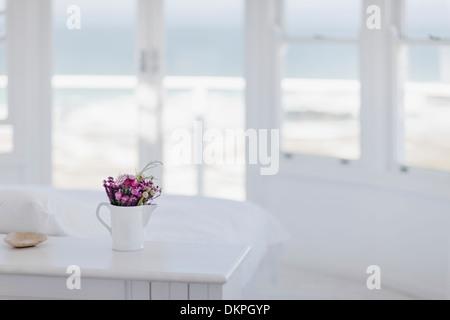 Vase of flowers on desk in bedroom overlooking ocean - Stock Photo