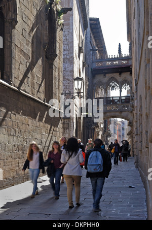People walking through narrow street in the old part of Barcelona. Catalonia. Spain - Stock Photo