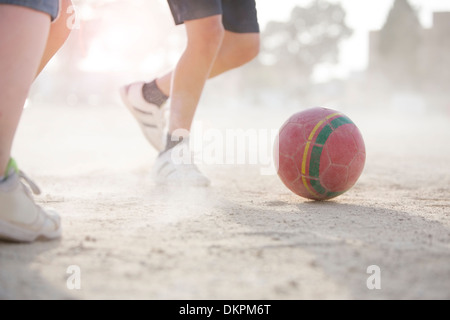 Children playing with soccer ball in sand - Stock Photo