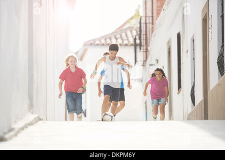 Children playing soccer in alley - Stock Photo