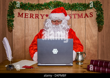 Santa sat at his desk in the North Pole doing some online Christmas shopping and answering his emails. - Stock Photo