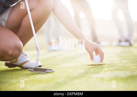 Woman removing golf ball from hole - Stock Photo
