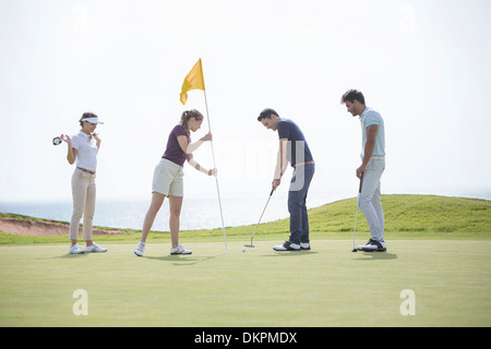 Friends putting on golf course - Stock Photo
