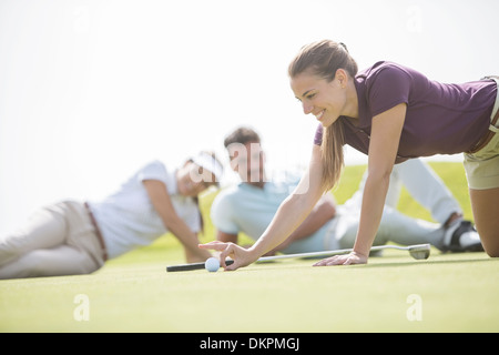Friends watching woman flick golf ball toward hole - Stock Photo