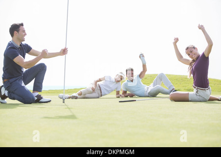 Friends cheering near hole on golf course - Stock Photo