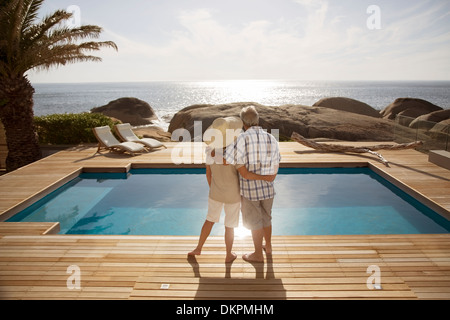 Senior couple hugging by modern pool overlooking ocean - Stock Photo